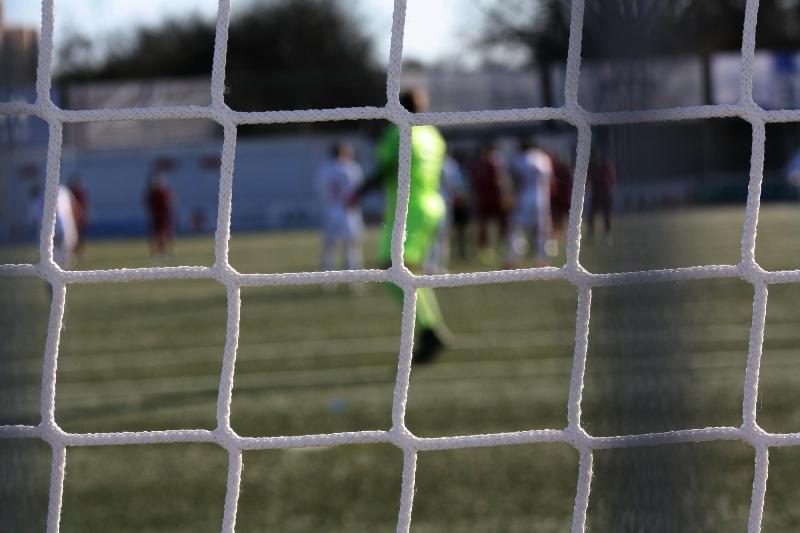 Rasen und Fußballspieler im Hintergrund und ein Tornetz im Vordergrund